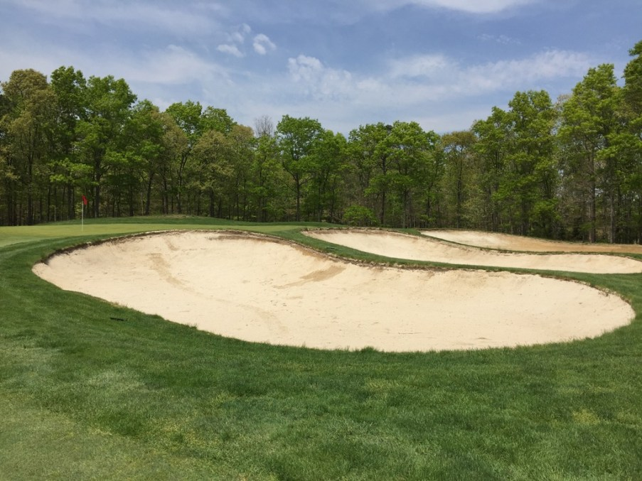 Triple sand traps guarding right side of 16th green.